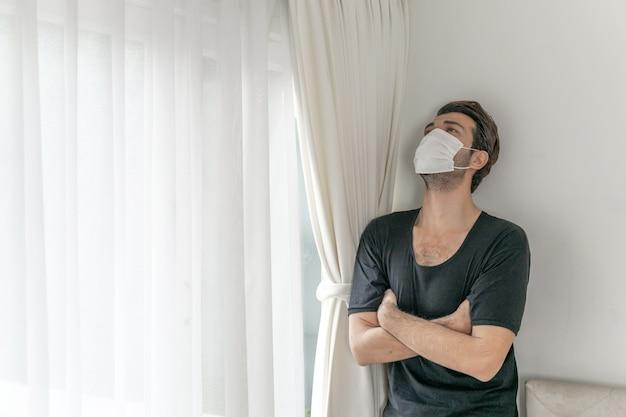 Uomo che indossa una maschera facciale per proteggere la sensazione di mal di testa e tosse a causa del coronavirus covid-19 nella stanza di quarantena