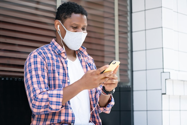 Man wearing a face mask and using his mobile phone while sitting at a store window on the street.