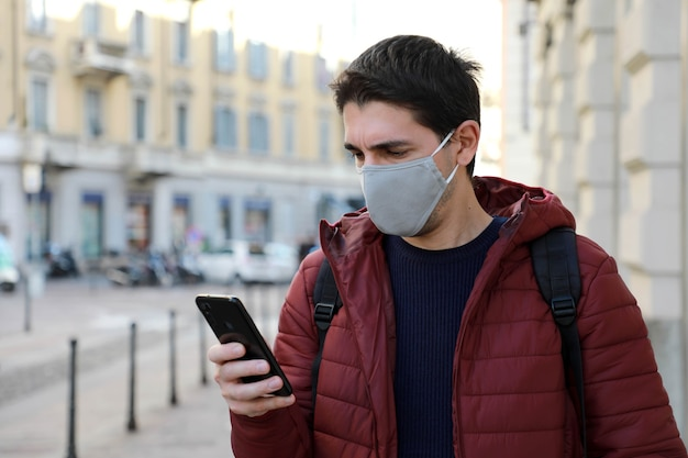 街を歩くときに携帯電話を使用してフェイスマスクを着用している男性