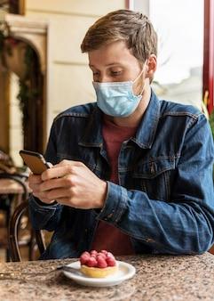 Uomo che indossa una maschera per il viso mentre controlla il suo telefono