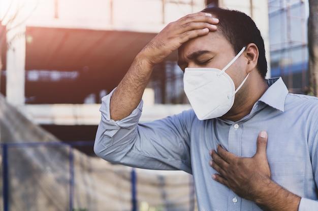 屋外で顔の衛生的なマスクの鼻を着ている男。大気汚染の概念。