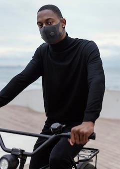 顔のマスクを着用し、自転車に乗る男