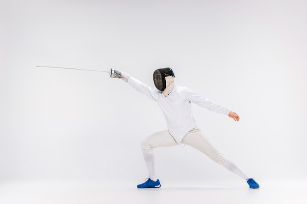 Man wearing fencing suit practicing with sword against gray