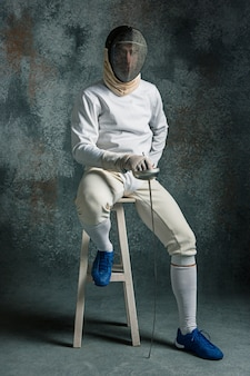 The man wearing fencing suit with sword