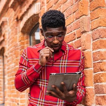 안경을 쓰고 그의 디지털 태블릿에서 읽는 남자