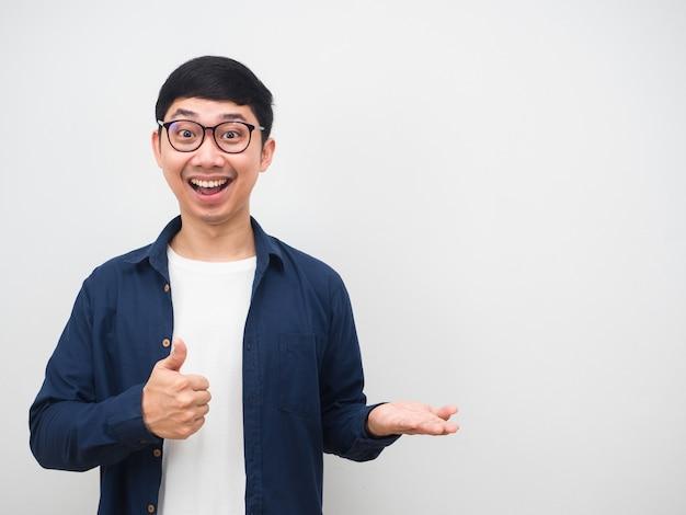 陽気な眼鏡をかけている男は、白い背景を保持するために親指を上に、空の手を上に表示します