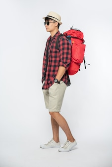 A man wearing glasses goes out to travel, wear a hat and carry a backpack