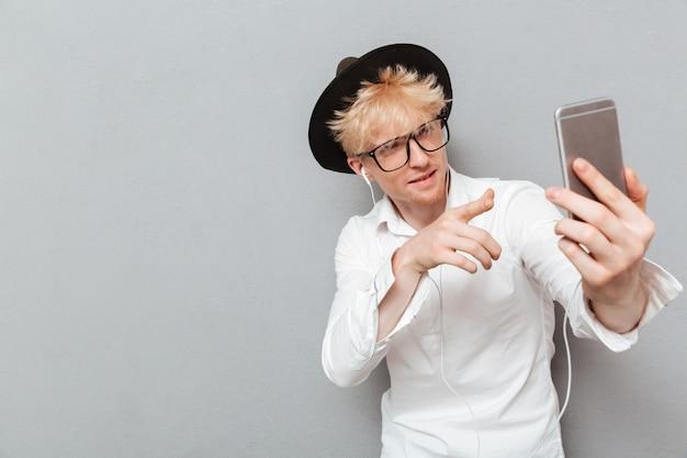 Man wearing glasses listening music while make selfie.