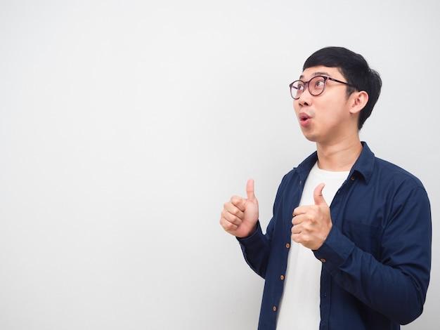 眼鏡をかけている男性は、興奮してコピースペースの白い背景を見て親指を表示します