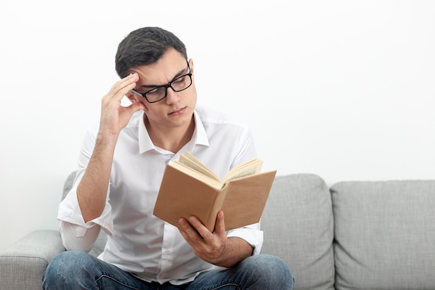 Man wearing glasses sitting on sofa and reading book