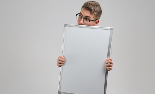 Man wearing glasses with clean magnetic board in his hands