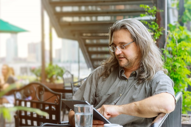 Man wearing glasses and working with touchpad while sitting in coffee shop