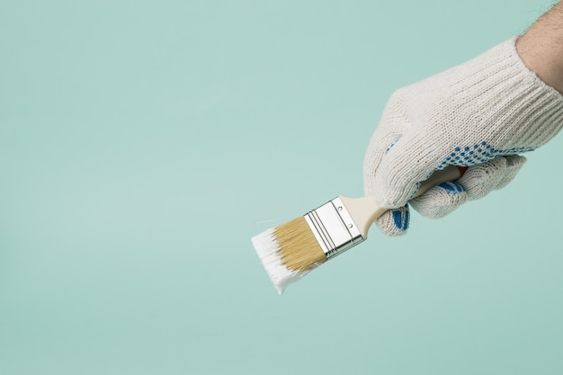 A man wearing gloves holds a brush with dripping white paint on a blue background. execution of painting works.