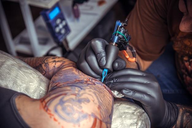 살롱에서 문신을 만드는 과정을 보여주는 장갑을 끼고 남자.