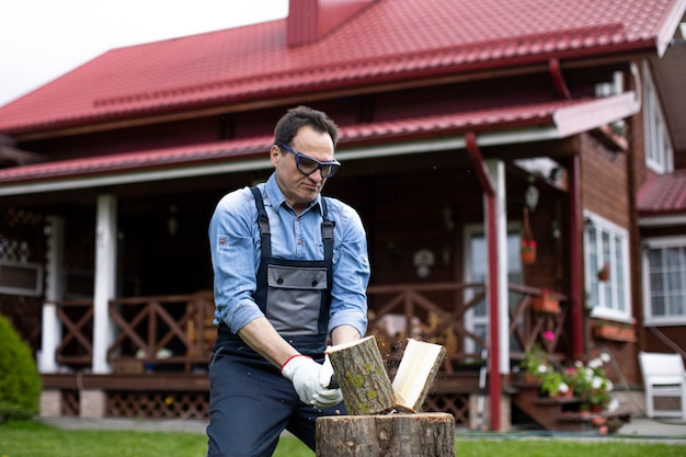 Man wearing goggles chopping wood against of beautiful wooden house