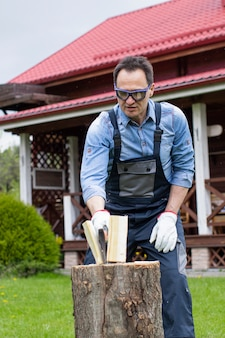 Man wearing goggles chopping wood in beautiful wooden house
