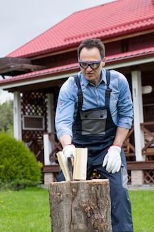 Человек в очках, рубить дрова в красивом деревянном доме
