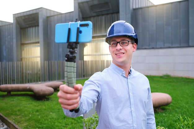 Man wearing a hard hat makes a live video with his mobile phone
