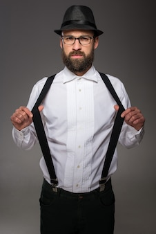Man wearing hat suspenders bow-tie