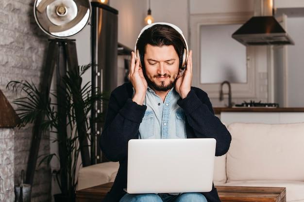 Наушники человека нося смотря цифровую таблетку сидя на кухне