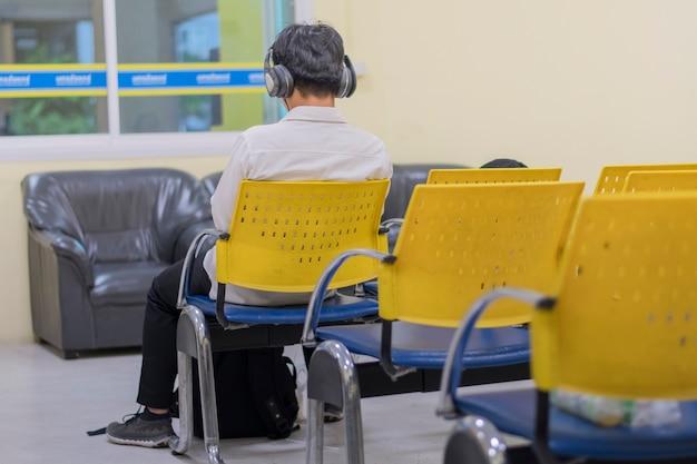 헤드폰을 끼고 노란색 의자에 혼자 앉아 있는 남자