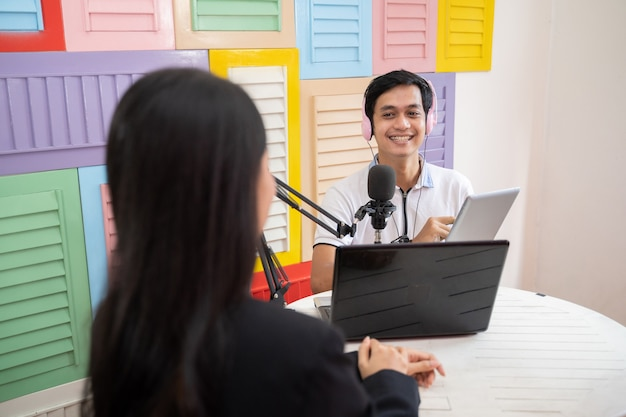 A man wearing headphones during a podcast with a woman