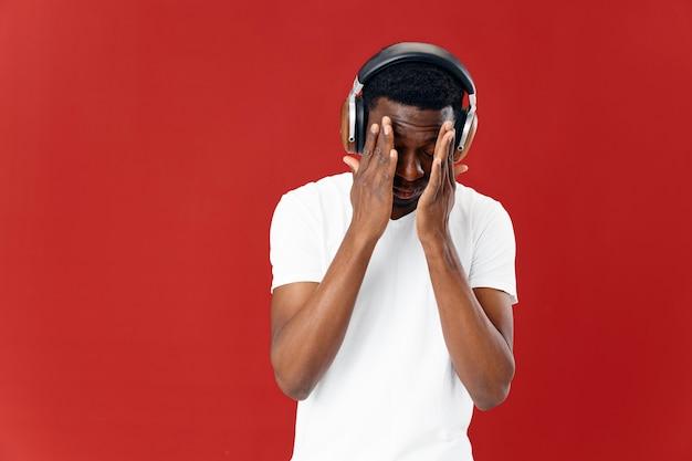 彼の顔の技術音楽赤い背景を保持しているヘッドフォンを身に着けている男