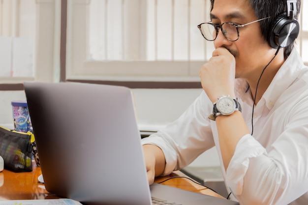 Наушники человека нося слушая к музыке пока работающ на портативном компьютере.