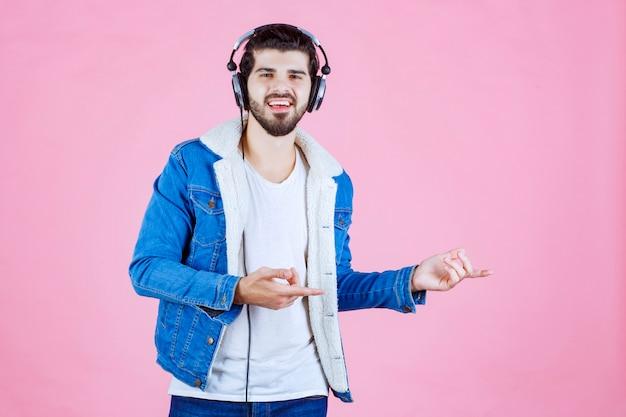 오른쪽에 누군가를 가리키는 헤드폰을 착용하는 남자