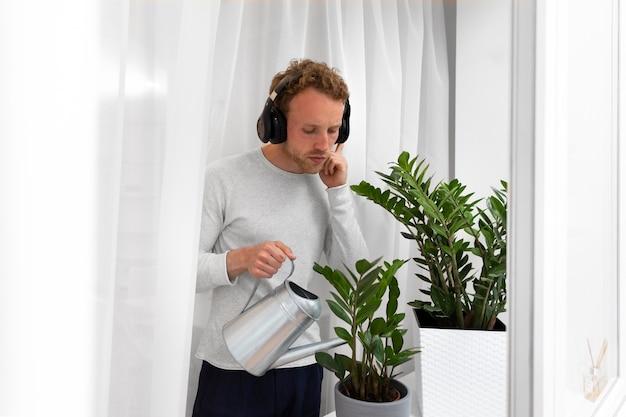 Человек в наушниках поливает растение