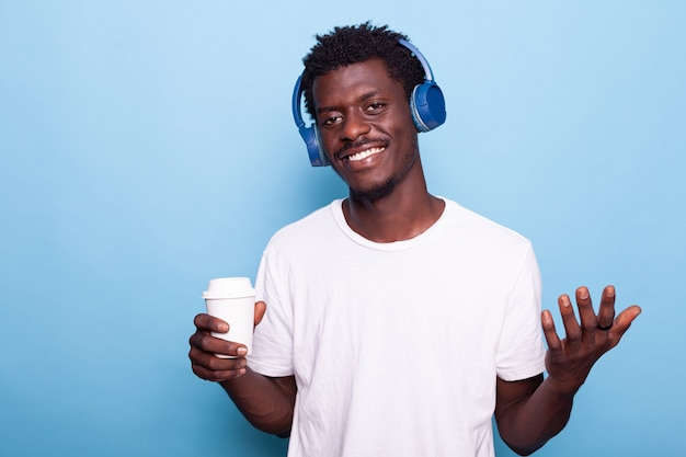 커피 한 잔을 들고 헤드폰을 끼고 있는 남자