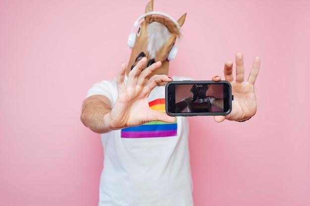 ピンクの背景を持つスタジオでスマートフォンからselfieを取りながら馬マスクを身に着けている男