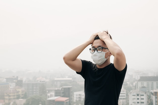 Man wearing hygiene mask and sick because of air pollution in the city.