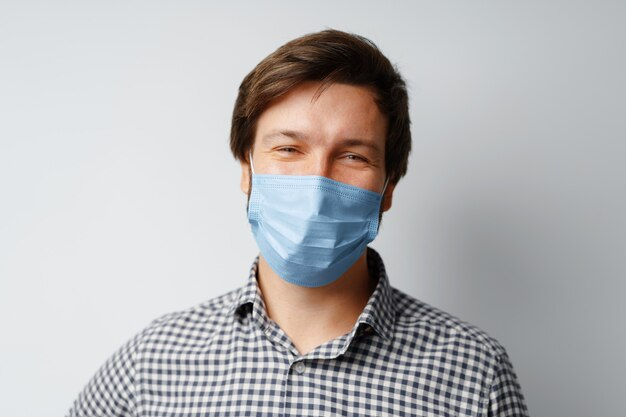 Man wearing hygienic mask against grey background