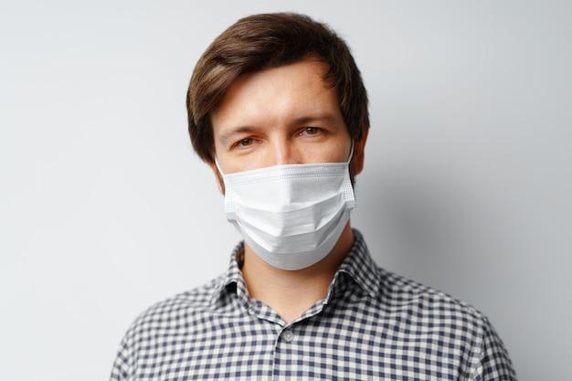 Человек в гигиенической маске на серой поверхности