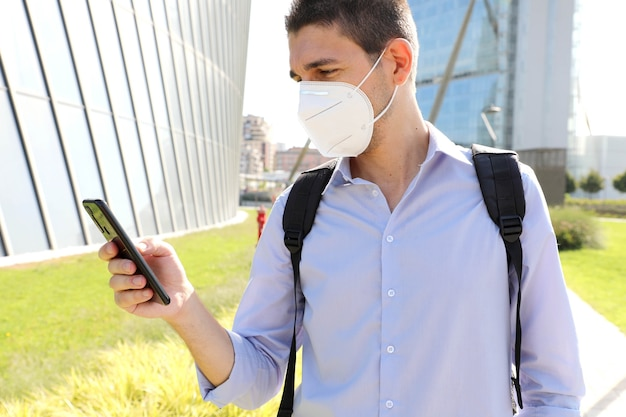 Man wearing kn95 protective mask using smartphone app