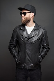 Man wearing leather biker jacket or asymmetric zip jacket with black cap, jeans and sunglasses. handsome hipster man over gray background.