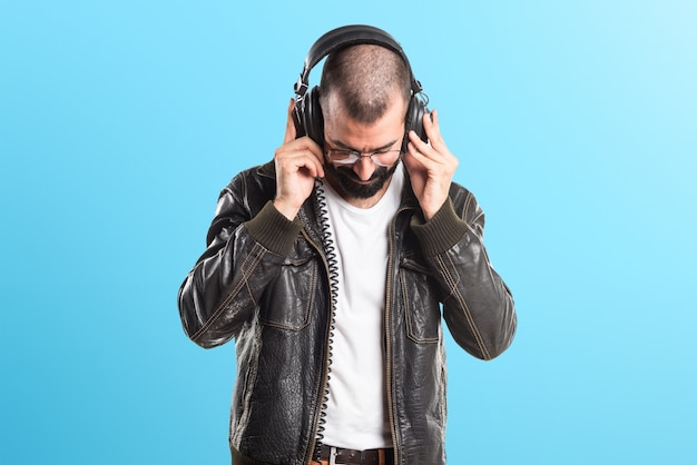 Man wearing a leather jacket listening music on colorful background