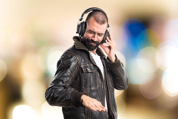 Man wearing a leather jacket listening music on unfocused background