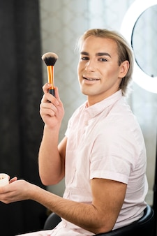 Man wearing make-up and holding a brush side view