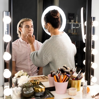 Man wearing make-up and make-up brushes