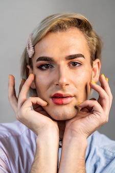 顔の半分に化粧をして身振りで示す男