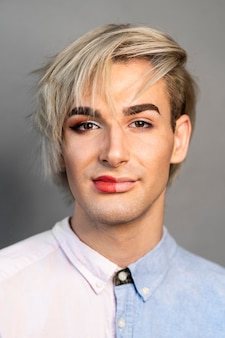 顔の半分に化粧をして別の服を着ている男性