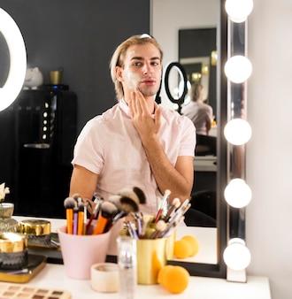Man wearing make-up using face cream