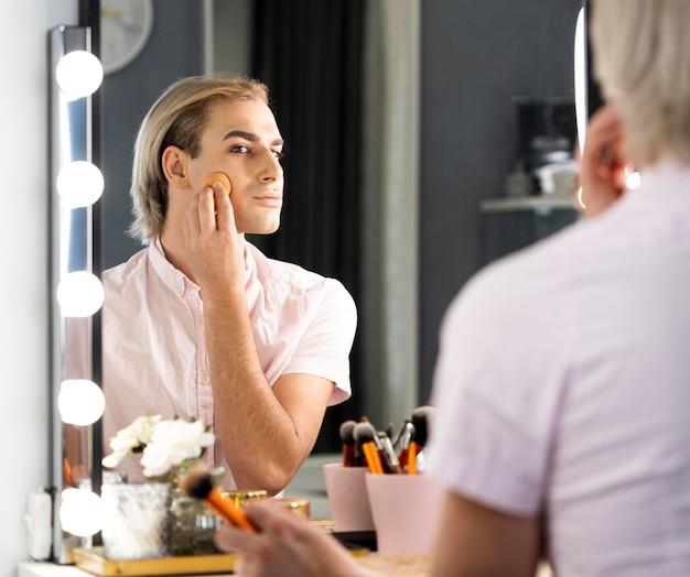 Uomo che indossa il trucco usando il fondotinta e guardandosi allo specchio