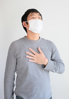 Man wearing mask get sick from corona virus, covid19 symptom as sneezing, cough, fever, body ache, breathing , pain.