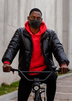 Man wearing a mask and holding his bike