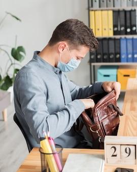 Uomo che indossa la maschera in ufficio durante la pandemia