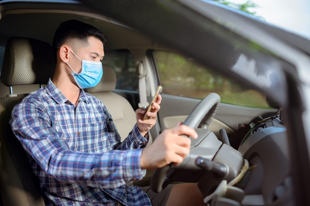 Man wearing a mask, press the mobile phone on the car. a man looking at the phone while driving.