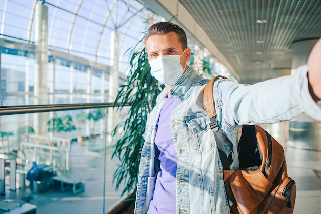 Man wearing a mask for prevent virus in international airport lounge waiting for flight aircraft.